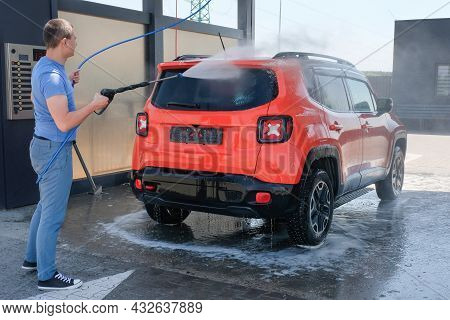 A Man Washing A Car With High Pressure Water At A Car Wash