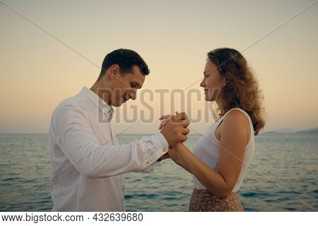 Young Adult Heterosexual Couple At Romantic Date. Young Adult Man And Woman Holding Hands Looking To