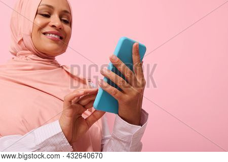 Smiling With Toothy Smile Mature Muslim Woman Of Middle Eastern Ethnicity In Pink Hijab With Smartph