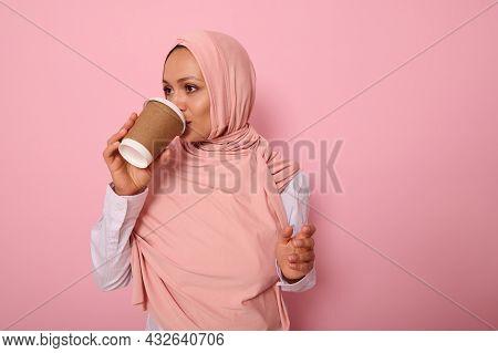Beautiful Arabic Muslim Woman Wearing A Hijab Drinking Hot Drink, Tea Or Coffee From Disposable Card