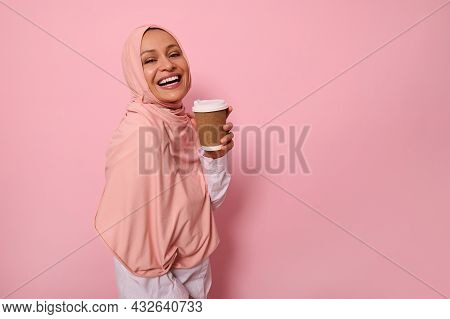 Charming Muslim Woman With Covered Head In Pink Hijab Holds Disposable Cardboard Takeaway Cup, Smile