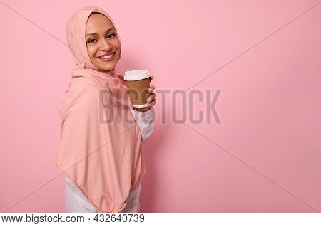 Arabic Muslim Cheerful Woman With Covered Head In Hijab Stands Three Quarters Against Pink Backgroun