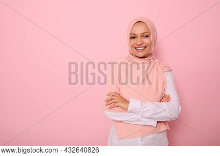 Arab Muslim Lady Wearing A Hijab Crossing Arms, Smiling With Beautiful Toothy Smile, Poses On Pink B