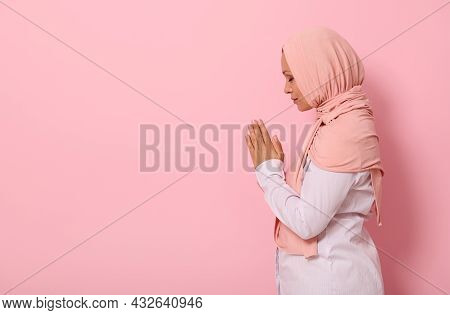 Side Portrait Of A Serene Muslim Arab Woman In Pink Hijab And Strict Outfit Praying, Performing Nama