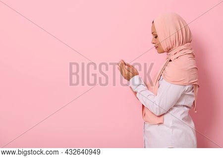 Side Portrait Of A Beautiful And Serene Muslim Arab Woman In Pink Hijab And Strict Outfit With Palms