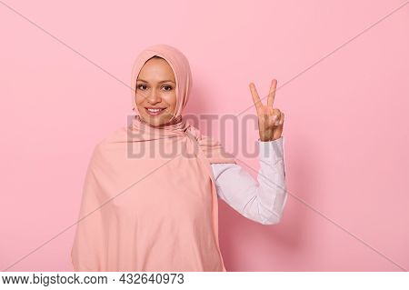 Attractive Friendly Arab Muslim Woman Wearing A Colored Hijab Showing Finger Peace Sign, Smiling Wit