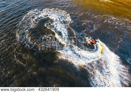 Aerial View Of Young Man Making Infinite Loop Riding On Fast Water Scooter On Sunset In Golden Water