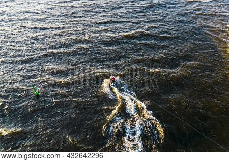 Aerial View Of Young Man Rides On Fast Water Scooter Jumping On Shallow Waves And Making Golden Spla