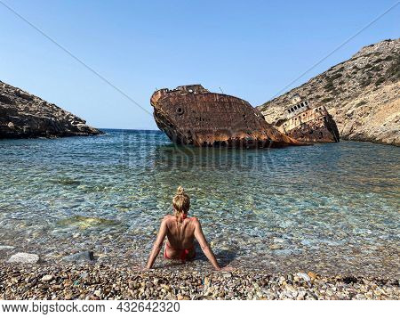 Back view on a woman wearing a red bikini looking at Shipwreck Olympia boat in Amorgos island during summer holidays, Cyclades, Greece. Travel background