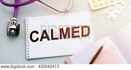 Stethoscope, Pills And Notebook With Calmed Word On Medical Desk.