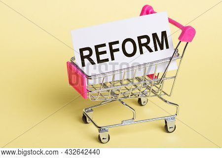 The Word Reform On A Card, On A Yellow Background With A Shopping Trolley.