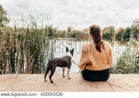 Teenage Girl In A Warm Sweater With Glasses Sitting On The Shore Of The Lake Looking Ahead - Autumn
