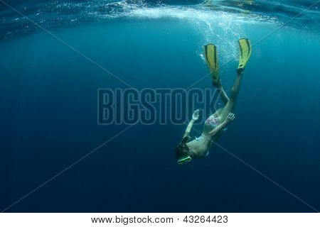 Young lady snorkeling and enjoying skin diving in a tropical sea