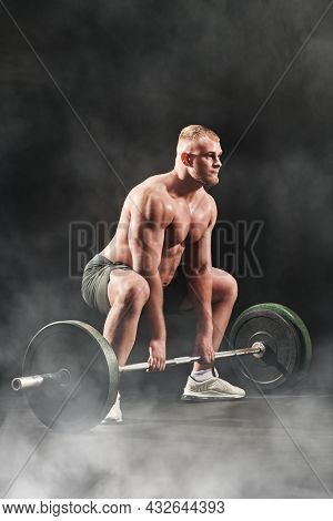 A male weightlifter lifts the barbell with effort. Professional sports. Weightlifting. Full length portrait on a black background.