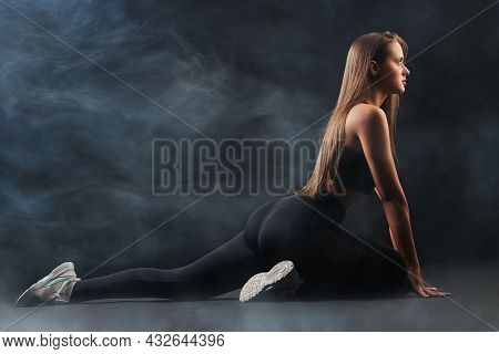 Full length portrait of a beautiful athletic girl doing stretching exercises on a black background. Sports and healthy lifestyle. Aerobics and fitness. Fitness trainer portrait.