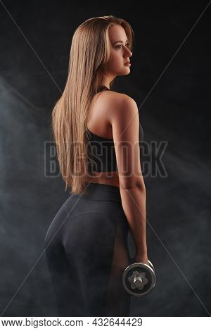 Sports and healthy lifestyle. Beautiful athletic girl standing with dumbbells on a black background. Fitness and aerobics. Fitness trainer portrait.