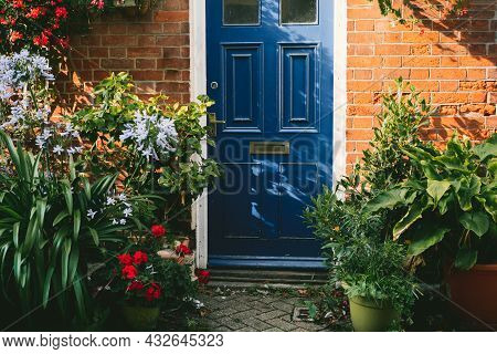 Blue Front Door And Brick Walls Facade Of A Beautiful Cottage With Many Various Potted Flowers. The
