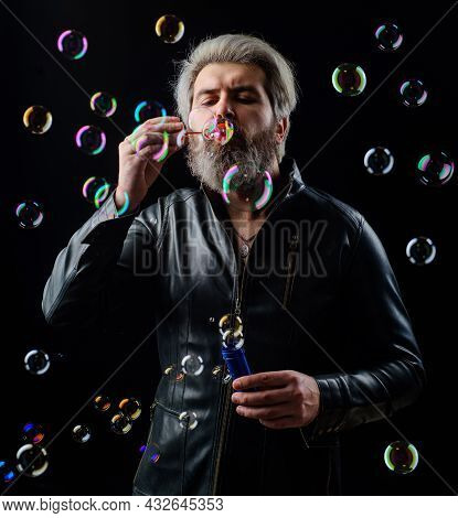 Man In Leather Jacket Blowing Soap Bubbles. Happiness. Good Mood. Childhood Concept. Bearded Guy Pla