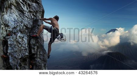 Young man climbing natural rocky wall with volcanoes on the background poster