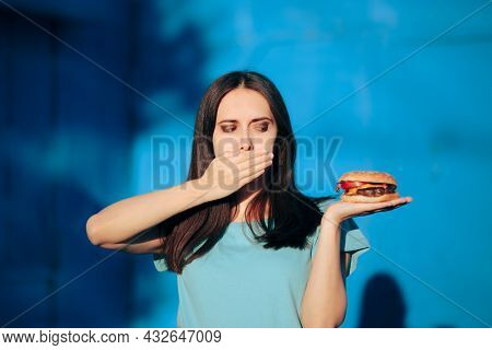 Woman Feeling Sick Covering Her Mouth After Eating A Burger