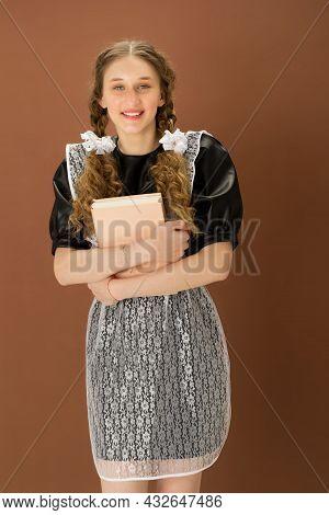 Cheerful Girl In School Uniform Holding Closed Book. Graduate Teenage Girl With Braided Hair Wearing