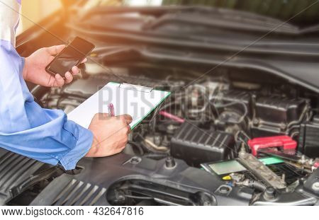 Hand Mechanic Hold Check Sheet Paper And Smart Phone For Basic Checking A Engine Of Car,maintenance