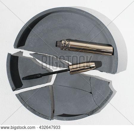 Lash Mascara On A Broken Cement Tray. Open Golden Mascara Tube On Concrete Background. Female Beauty