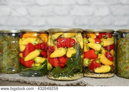 Mini Chili Peppers Of Red, Yellow And Orange Colors, Canned In Glass Jars With Herbs, On A Wooden Ta