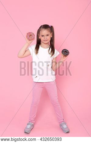 Cute Little Girl With Long Brunette Hair Having Fun To Camera With Donuts Isolated On Pink Backgroun