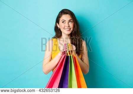 Young Dreamy Woman Thinking Of Buying New Things, Holding Shopping Bags And Smiling, Standing Agains