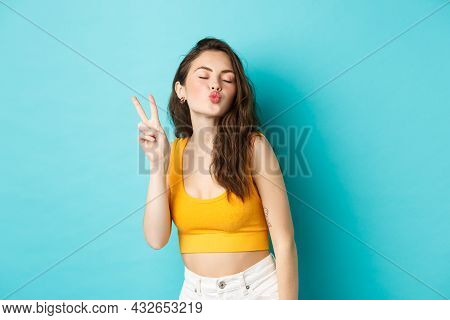 Glamour Girl In Summer Clothes Close Her Eyes And Making Kissing Face With V-sign, Enjoying Vacation