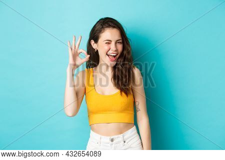 Young Cheerful Lady In Summer Clothes Winking And Saying Yes, Alright Gesture, Making Ok Sign In App