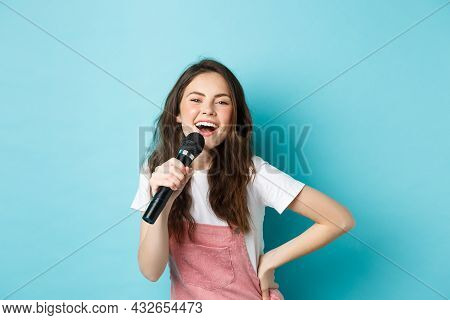 Cheerful Young Woman Singing Karaoke, Holding Microphone And Smiling, Having Fun, Standing Over Blue