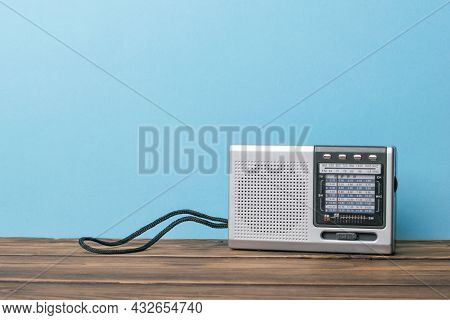 Silver Retro Radio On A Wooden Table On A Blue Background. Vintage Radio Equipment.