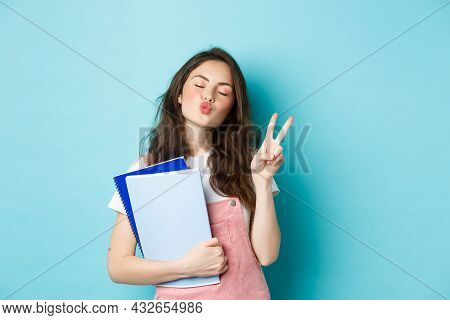 Education Concept. Smiling Glamour Girl Pucker Lips For Kiss, Showing V-sign Peace And Holding Noteb
