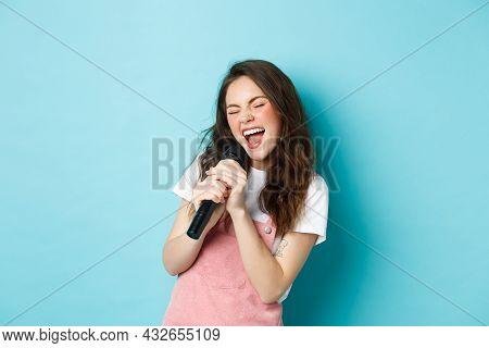 Beautiful Girl Singer Holding Microphone, Singing Karaoke In Mic, Standing Over Blue Background
