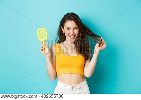 Happy Attractive Woman Showing Her Brush Without Hair Strand And Touching Healthy Long Hairstyle Wit
