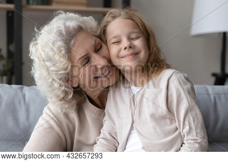 Affectionate Old Grandmother Cuddling Little Grandchild At Home.
