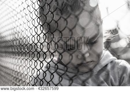 Black And White Photo Of A Little Girl With A Sad Look Behind A Metal Fence, Social Problems, Raisin