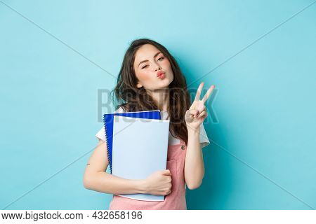 Portrait Of Glamour Girl Showing Kissing Face And V-sign, Carry Notebooks Homework Material, Standin