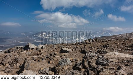 Volcanic Rocks Are Scattered Along The Mountainside, Devoid Of Vegetation. In The Distance, Against