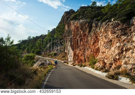 Hiking on Lycian way trail route from Finike to Karaoz. Man is trekking on mountain road with high dramatic cliff, Eco tourism in Turkey