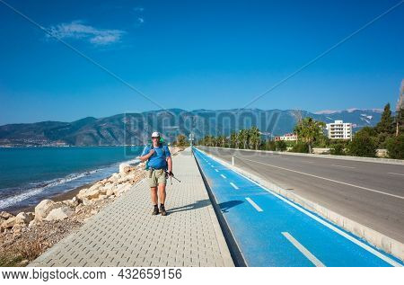 Hiking on Lycian way trail. Man with backpack trekking along Finike long beach on walkway next to road, Mediterranean coast of Turkey