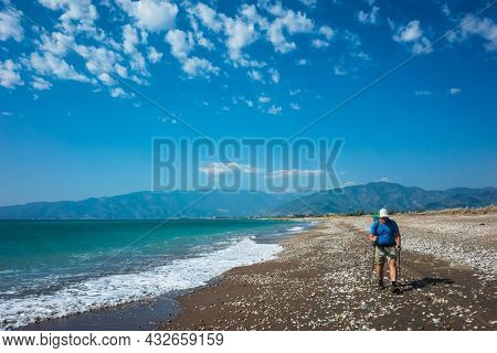 Hiking on Lycian way trail. Man with backpack trekking along long Finike beach, Mediterranean coast of Turkey, Eco tourism in Turkey
