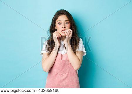 Portrait Of Scared And Startled Brunette Girl Biting Fingernails, Staring At Camera Shocked And Worr