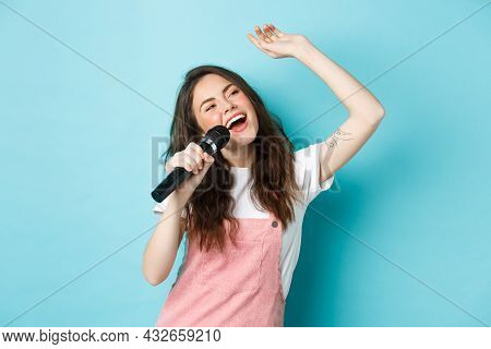Beautiful Female Singer Holding Microphone, Singing Karaoke In Mic, Standing Over Blue Background