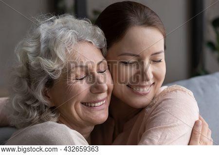 Close Up Head Shot Devoted Old Mother Cuddling Grownup Daughter.