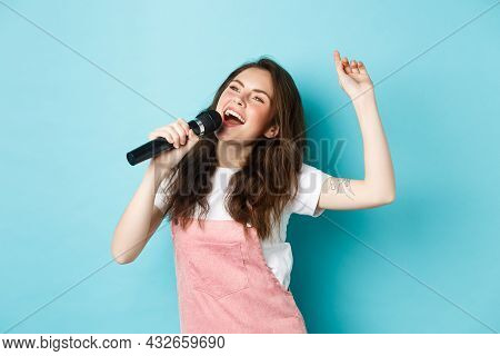 Happy Young Woman Perform Song, Singer Holding Microphone, Dancing And Singing At Karaoke, Standing