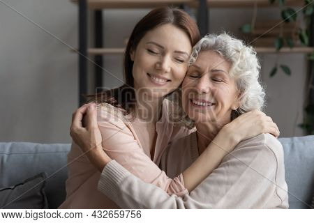 Affectionate Young Woman Cuddling Older Mother At Home.