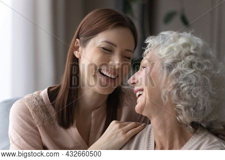 Attractive Young Woman Cuddling Smiling Older Retired Mother